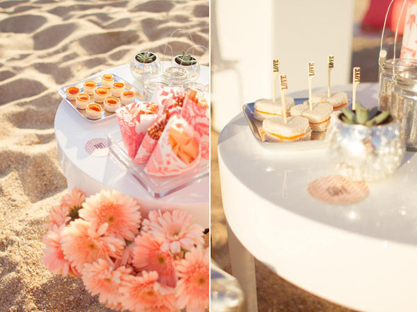 pink flowers and finger food on the beach