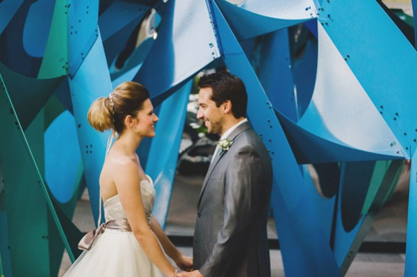 bride and groom in front of art