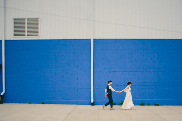 bride and groom with blue wall in williamsburg
