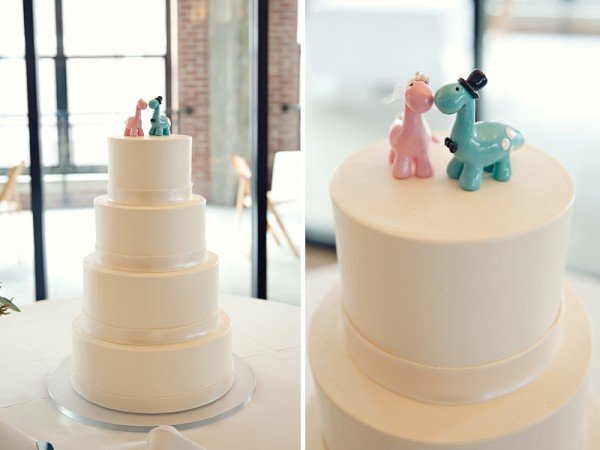 simple white wedding cake with dinosaur cake toppers