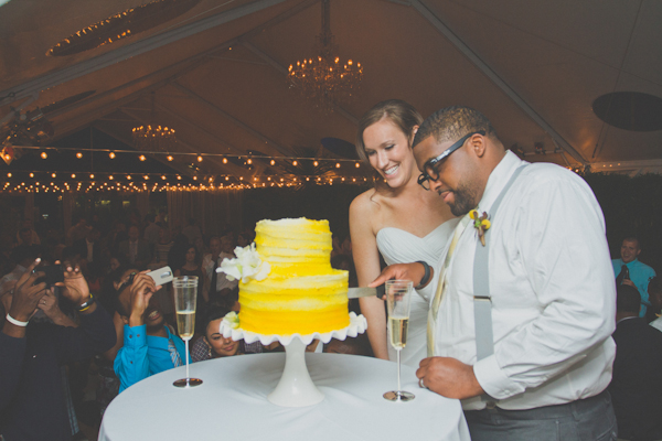 cutting the yellow wedding cake